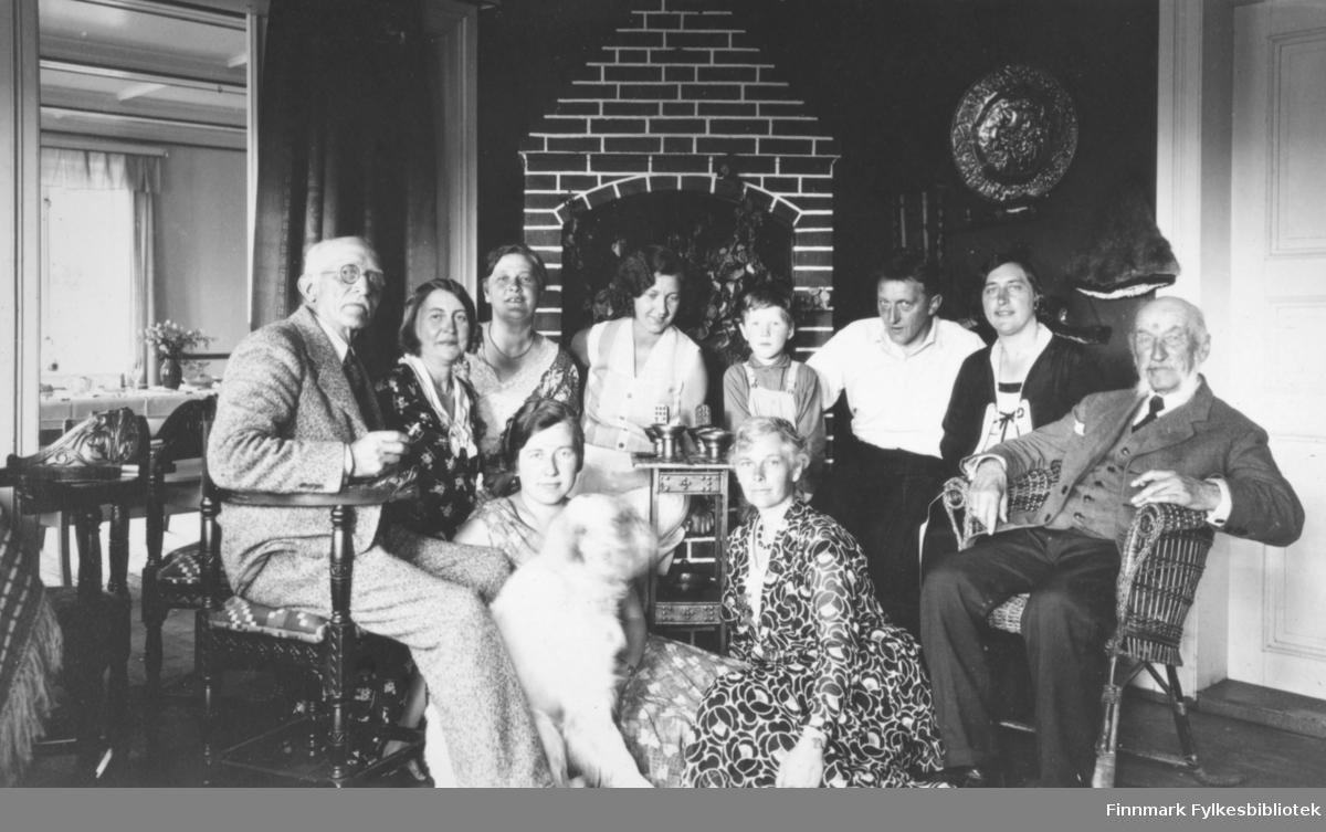 Samling i en halvsirkel foran peisen i huset Saga. Åtte personer sitter i pinne- og kurvstoler. To damer og en hund sitter på gulvet. De to eldre herrene på hver side av halvsirkelen har dresser på seg. Han til venstre i en lys og han til høyre mørk med hvit skjorte og slips. Damene som sitter på gulvet har mønstrete kjoler på. Gutten i midten har skjorte og snekkerbukse. Hun ved siden av han har skjørt og lys overdel. De to damene til venstre på bildet har mørke, mønstrete overdeler på. Mannen til høyre for gutten har mørk bukse og hvit skjorte. Hun til høyre har mørk jakke og mønstret skjorte/overdel. En dør til høyre er lukket, men den til venstre står åpen og man ser inn på et kjøkken el. spisestue med stoler, et bord med duk og en blomstervase. Peisen bak folkene er pent murt og skrår innover mot taket. En pyntegjenstand av metall henger på veggen til høyre for peisen.