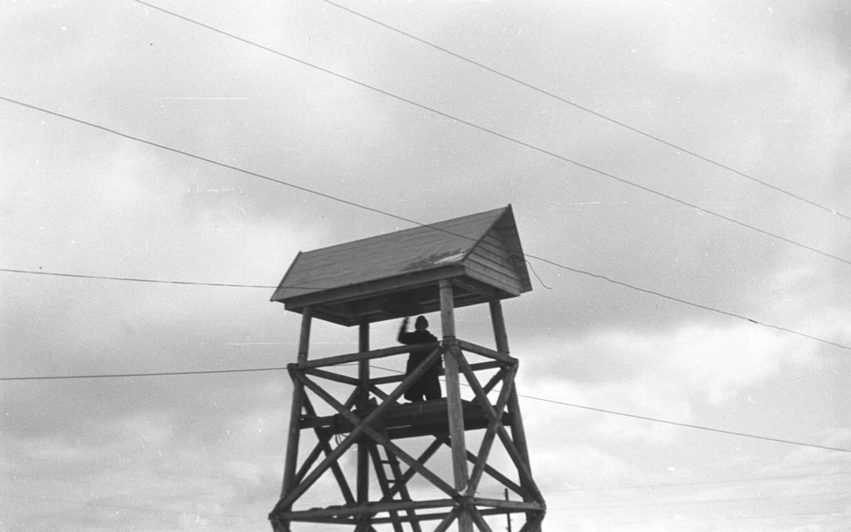 Klokketårn i Vadsø. En ukjent mann er oppe i det og ringer med klokka.