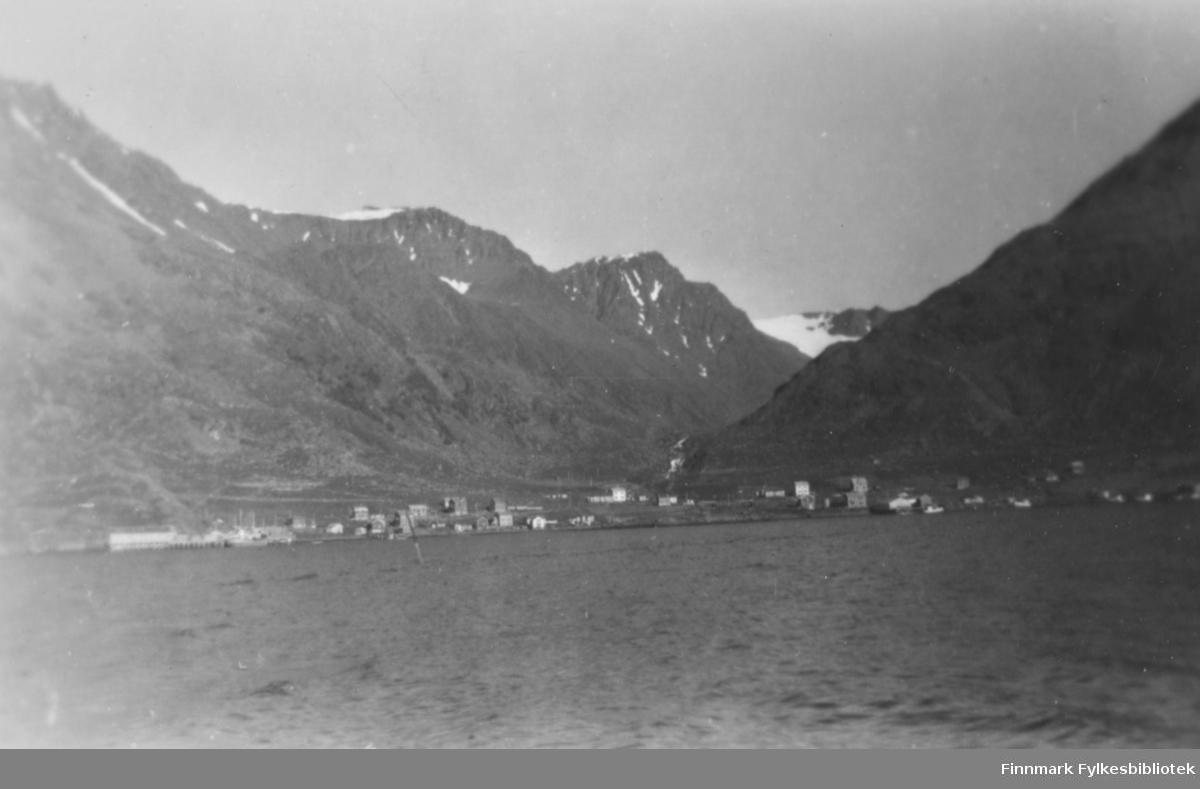 Bergsfjord i Loppa fotografert fra sjøen. Husene ligger i strandkanten med høye fjell i bakgrunnen. Noen litt større bygg til høyre på bildet, som muligens er næringsbygg. Noen snøflekker ligger i fjellene, men ellers bart. Det er små bølger på sjøen som tilsier lite vind og det er skyfri himmel.