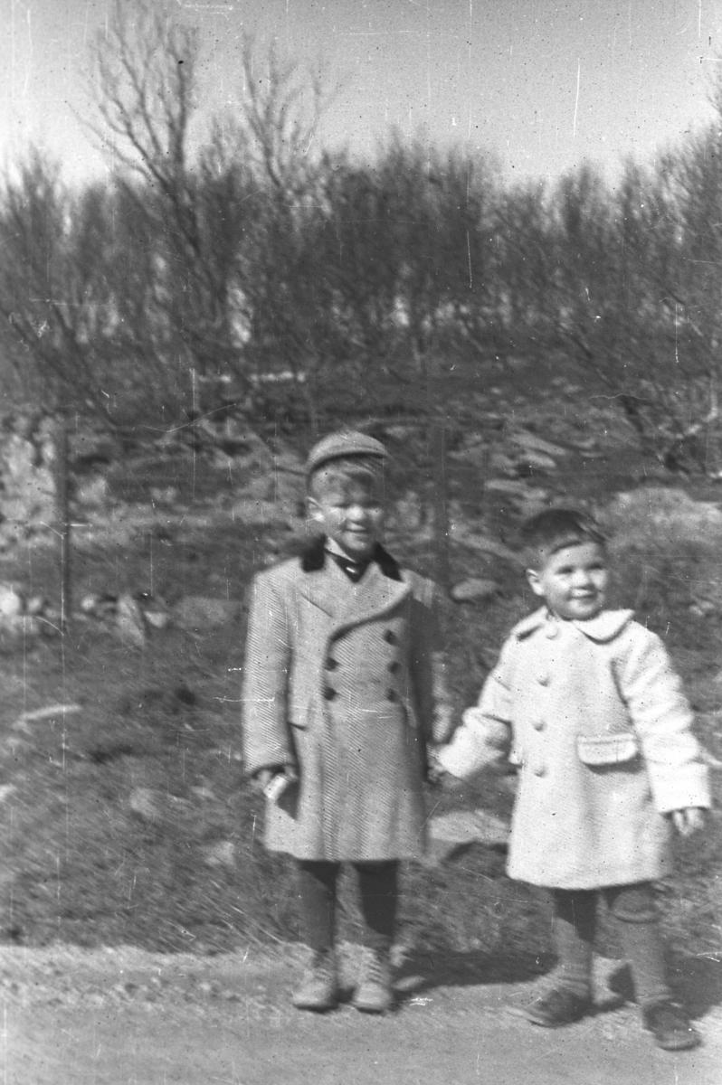 To gutter fotografert mens de står i veikanten. Sted og personer er ukjent, men guttene kan være Øystein og Rolf Hauge.
