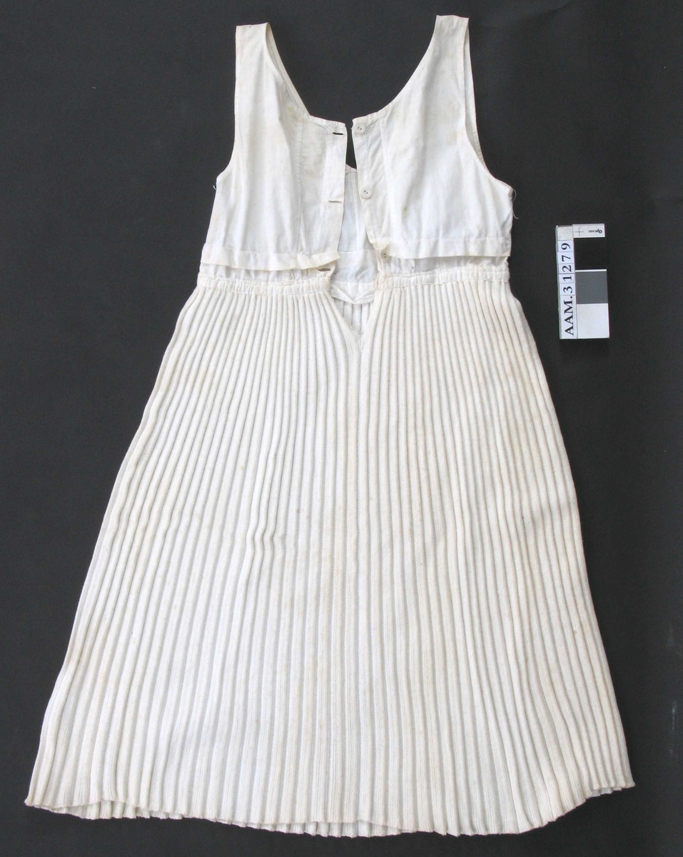 Maskinstrikka plisséskjørt , påsydd ermeløst livstykke med knepping i ryggen. Et legg sydd på tvers av dette, tydeligvis for å gjøre kjolen kortere.