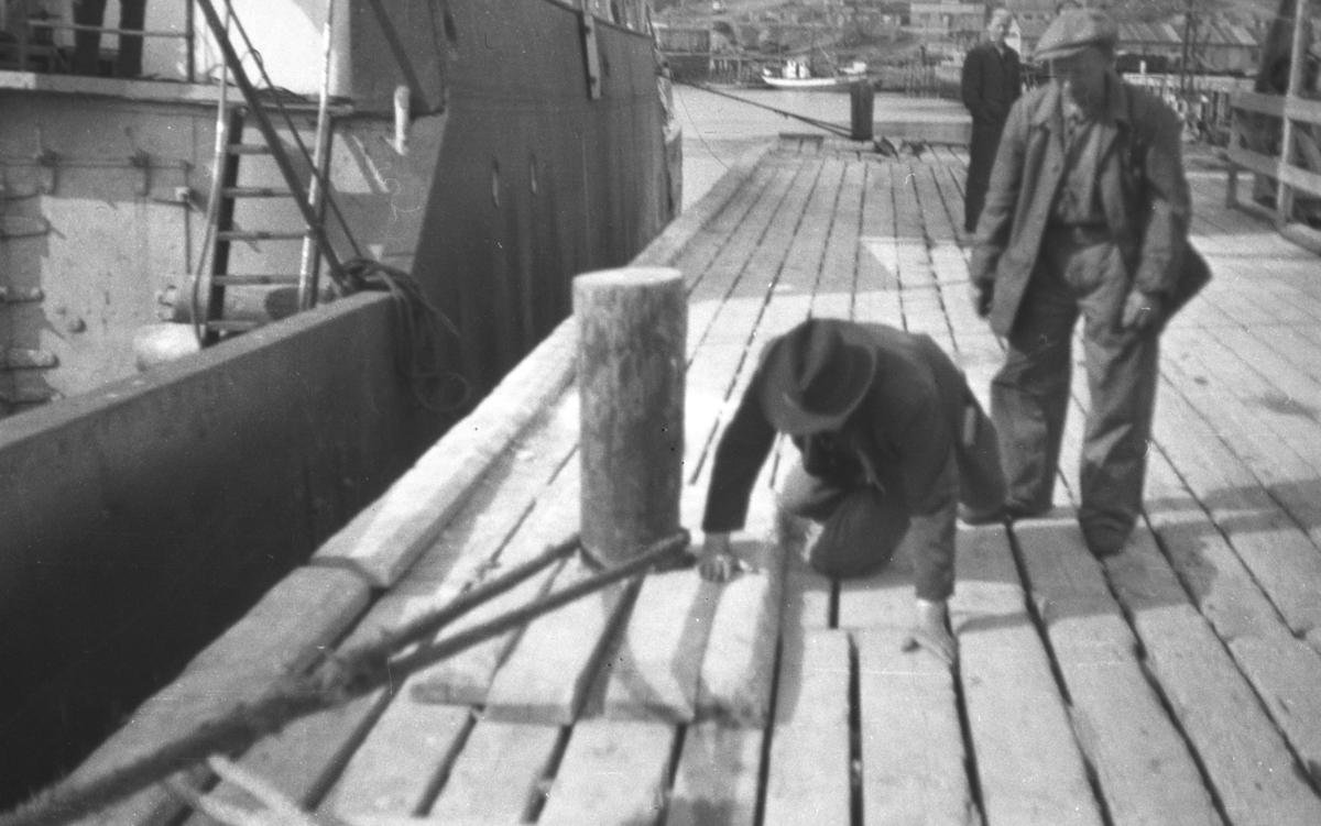 Tre ukjente menn fotografert på en kai ved siden av et stort skip. Personer og sted er ukjent.