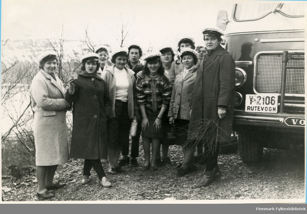 Vadsø damekor tar en pause på bussturen til sangerkorstevnet i Berlevåg 1962. Identitetene til noen av personene i bildet er noe usikkert. Første rekke fra venstre: Alfhild Ballo, Selma Thomasen, Aslaug Aronsen, ukjent, Gunnvor Arensen (?) og Ingrid Niskavara. Bakerste rekke fra venstre: Lisbeth (Lissi) Esbensen, Liv Bjørgan Pedersen, Aslaug/Astrid (?) Karlsen, Gunnvor Dahl og ukjent. Damene bærer hvite sangerluer. Ingrid Niskavara, helt til høyre, holder på noen kvister. Bak henne kan man se bussen. Y-2106 var en Volvo personbuss, 1960-modell, som tilhørte A/S Polarbil i Vadsø. Polarbil har historie tilbake til 1920. Det hadde rutetrafikk i Øst-Finnmark. 1. januar 1976 ble selskapets ruter overtatt av FFR - Finnmark Fylkesrederi og Ruteselskap.