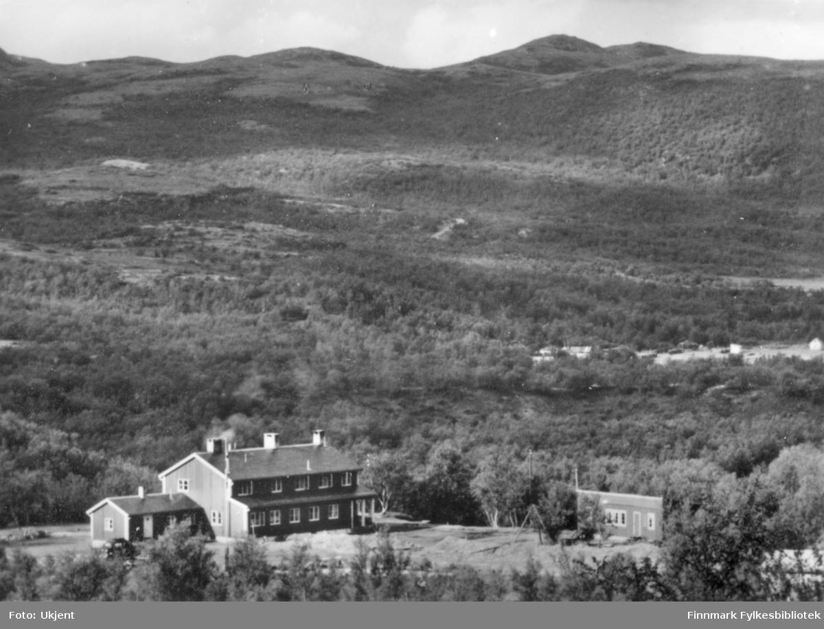 Et oversiktsbilde av Ifjord gjestgiveri. På gjestgiveriet kan man se flere piper, vindu og dører. Bygningen er omringet av skog.