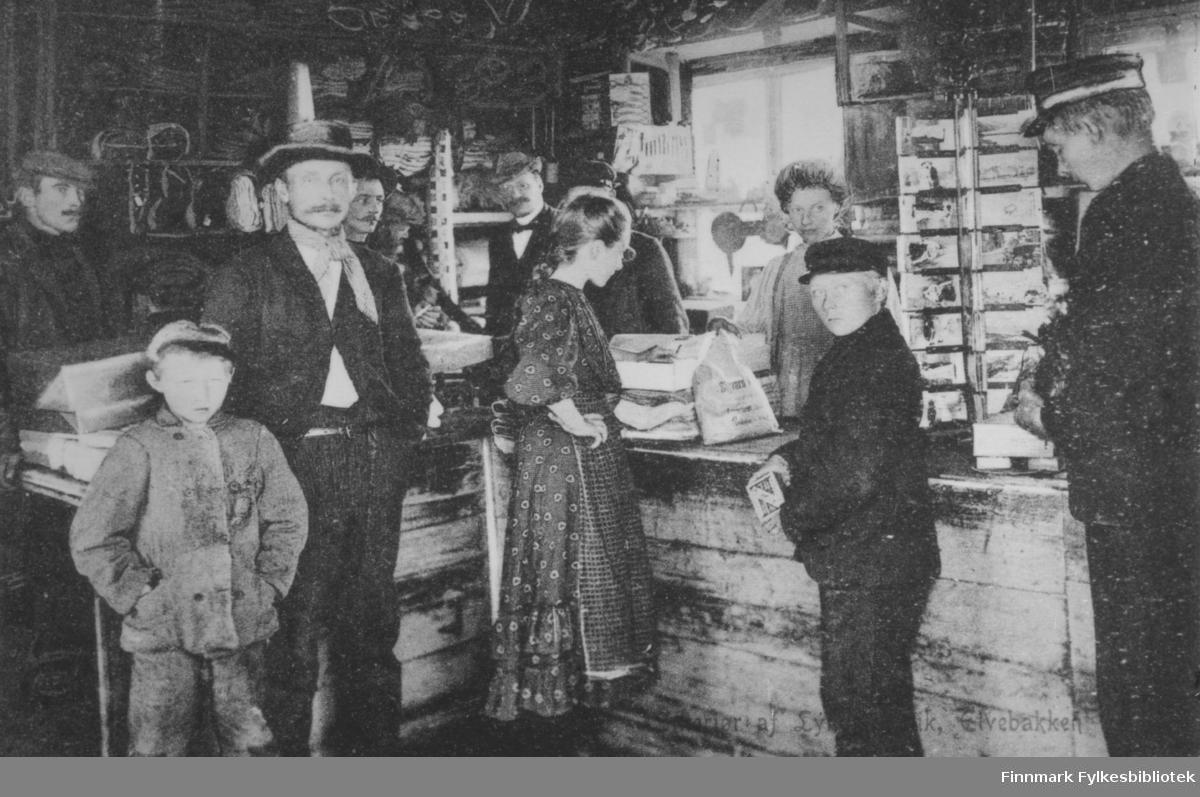 Lyngbutikken på Elvebakken. Dette bildet har også Alta museum. Gutten som står som nummer to fra høyre er Andreas Julius Johansen f. 1895. Han er far til giver av bildene, Karen Kristine Jakobsen. På bildet er han ca. 14-16 år. I hånden har han en fyrstikkeske. I butikken er det seks menn, to gutter, ei jente som handler, og en kvinne som ekpederer. Disken er av tre