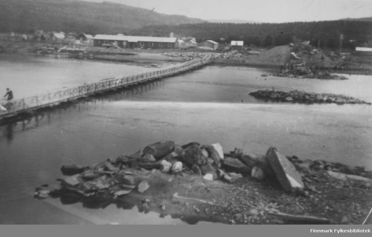 Provisorisk bru over Altaelva. Over elven er det en smal bro med rekkverk. På broen er det en person på sykkel. En del hus ses på den andre siden. Fremst mot elven er det en lang bygning. I elven ligger det steiner. I bakgrunnen av bildet er det fjell, og skog