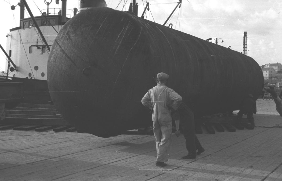 """Et av Bergenskes lasteskip, """"Luna"""" eller """"Mercur"""" har losset Esbensen-tanken på kaia i Vadsø. Flere ukjente menn står på kaia og hjelper med lossing/plassering av tanken."""