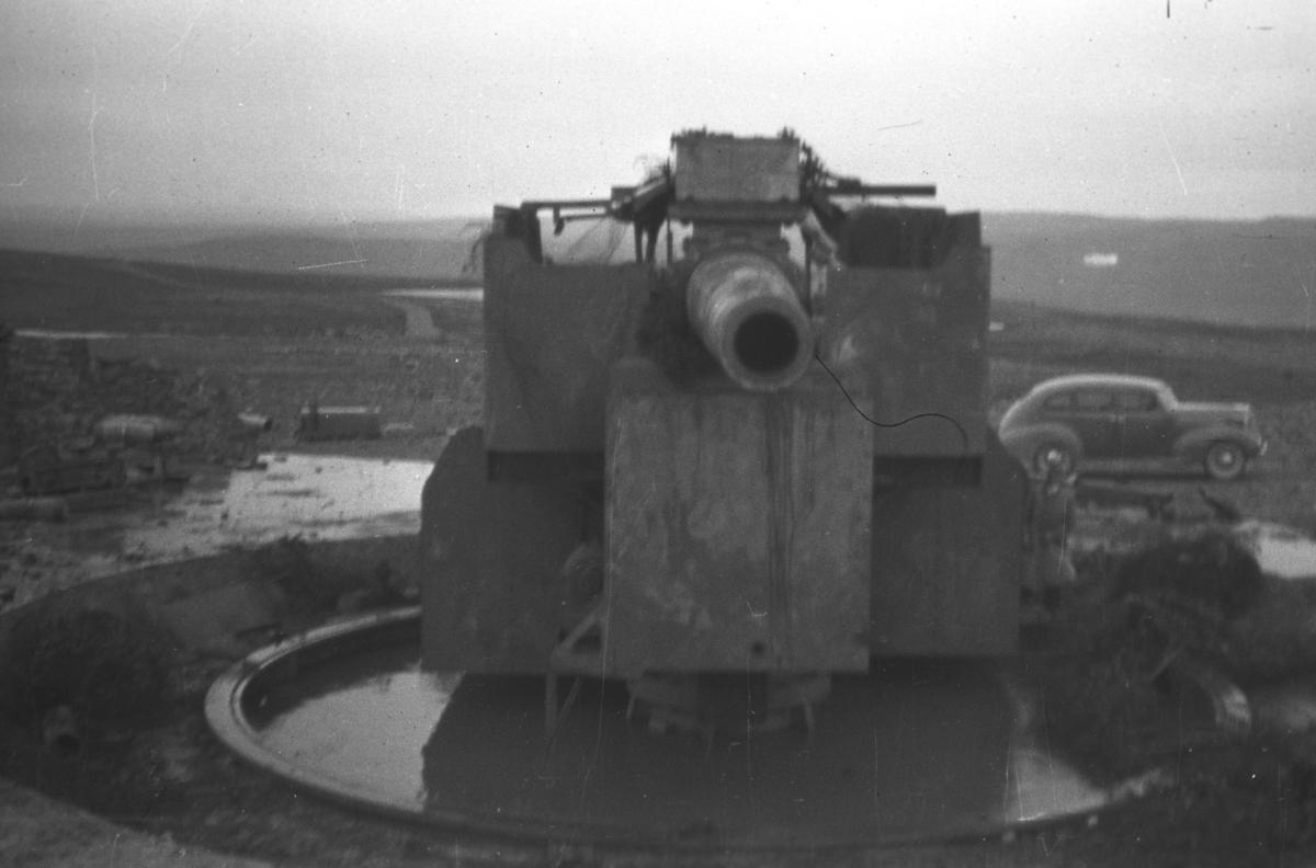 Ett av hovedskytsene ved kystfortet på Kiberg -tatt etter frigjøringen. Kanonen har et kaliber 28 cm og skuddvidde på 35 kilometer. Kiberg Kystfort var det største i Finnmark med tre slike kanoner. Til høyre i bakgrunnen står det en 1950-talls bil parkert.