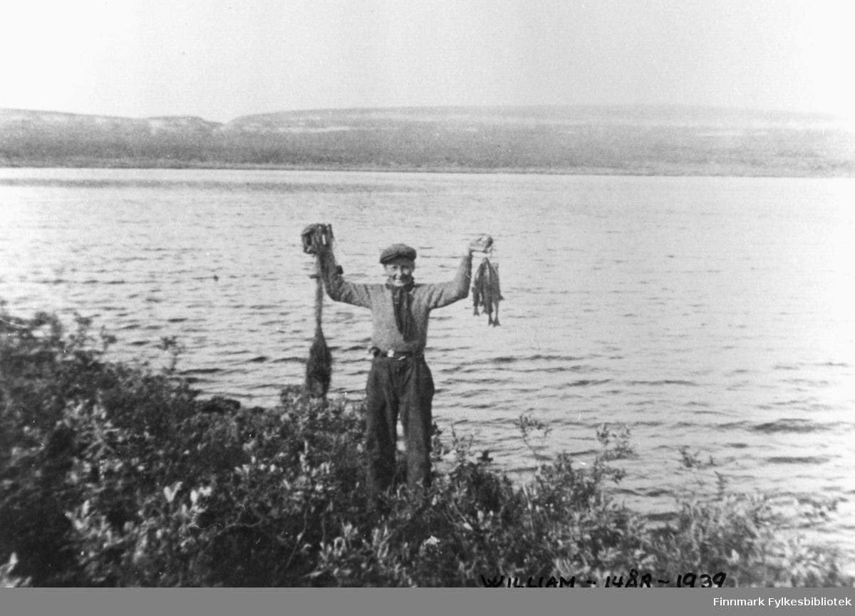 William Mietinen 14 år på fisketur i Østervann ovanfor Vestre Jakobselv. Han står ved vannet og løfter opp en bunt av fisk (ørret?). På den andre handen holder han garn. Han ser veldig fornøyd ut. Bak vannet ser vi fjellet.
