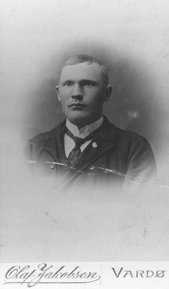 Portrett fra en mann, Johannes Ittelin. En liten plastblomst på krage, slips og hvitt skjorte.