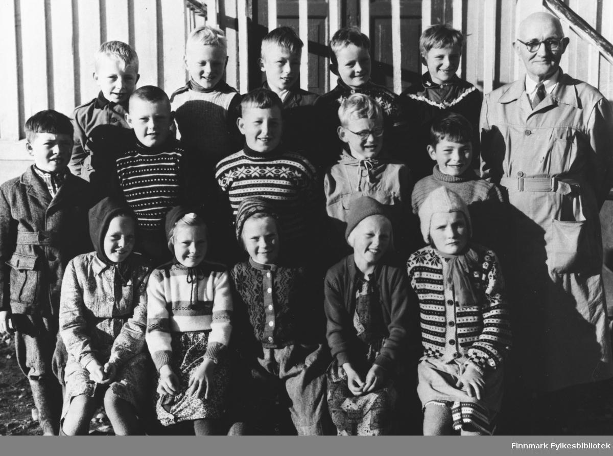 Klassebilde fotografert ved skolen i Vestre Jakobselv en deilig vårdag. Lærer Olav Bugge Granaas og 15 barn har samlet seg til gruppebilde.  På første rekke sitter fem jenter, fra høyre Eirin Henninen og Solveig Henninen.  Andre rekke (bak jentene) fra venstre: Harald Hansen, Odd Reisænen, Svein Karvo, Åge Henninen og Bernt Dikkanen.  Bakerste rekke fra venstre: ukjent, Erland Pedersen, ukjent, ukjent, Lars Pedersen og så lærer Olav Bugge Granaas helt til høyre i bildet.