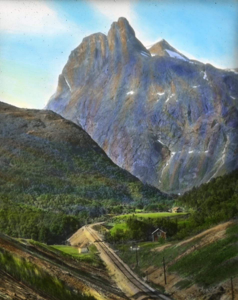 Håndkolorert dias. Utsikt over dalføre i Romsdal. Et jernbanespor går innover i dalen. I bakgrunnen sees Romsdalshorn.