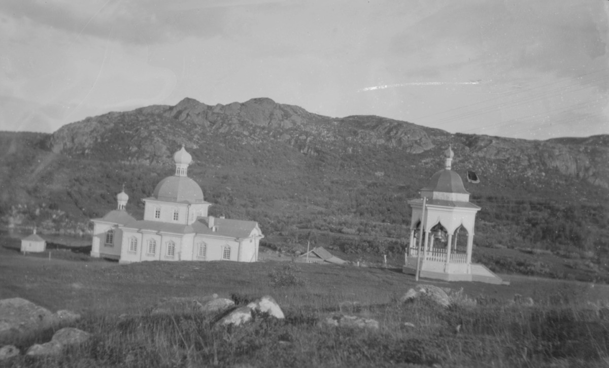På bildet ser vi Kristi fødsels kirke i Nedre Kloster, Petsjenga. Petsjenga (finsk Petsamo, russisk Печенга, nordsamisk Beahcán, skoltesamisk Peäccam) i den sørlige delen av Pasvikdalen er det et russisk område på 10 470 kvadratkilometer i distriktet med samme navn. Distriktet  ligger i Murmansk oblast og grenser mot Norge. Kirken ble bygget 1908-11, ødelagt i brann 2007. Treenighetskirken sto i Øvre Kloster.