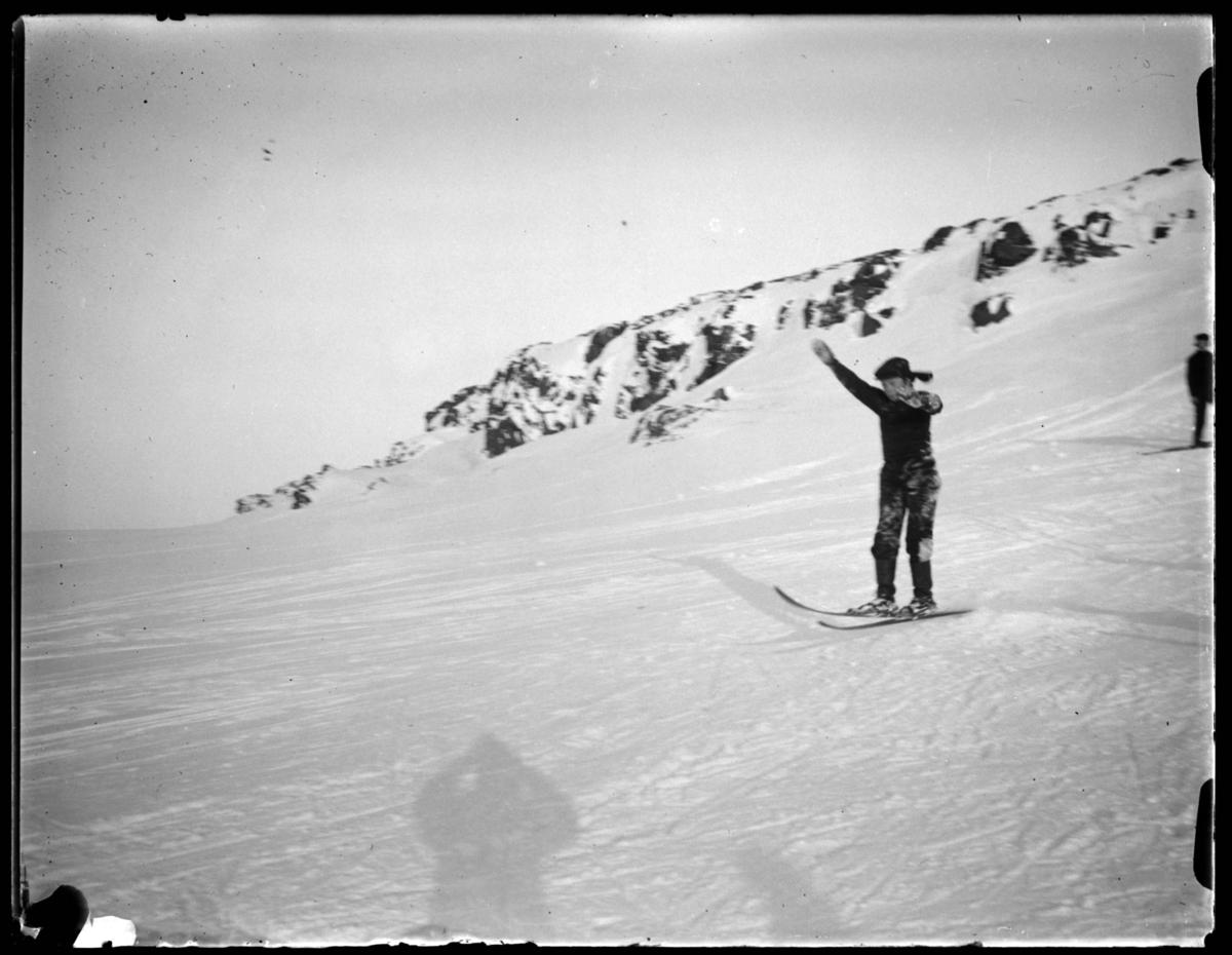 Gutt som renner på ski. Han er midt i svevet etter et lite hopp. Se også bilde FB.83002-127.