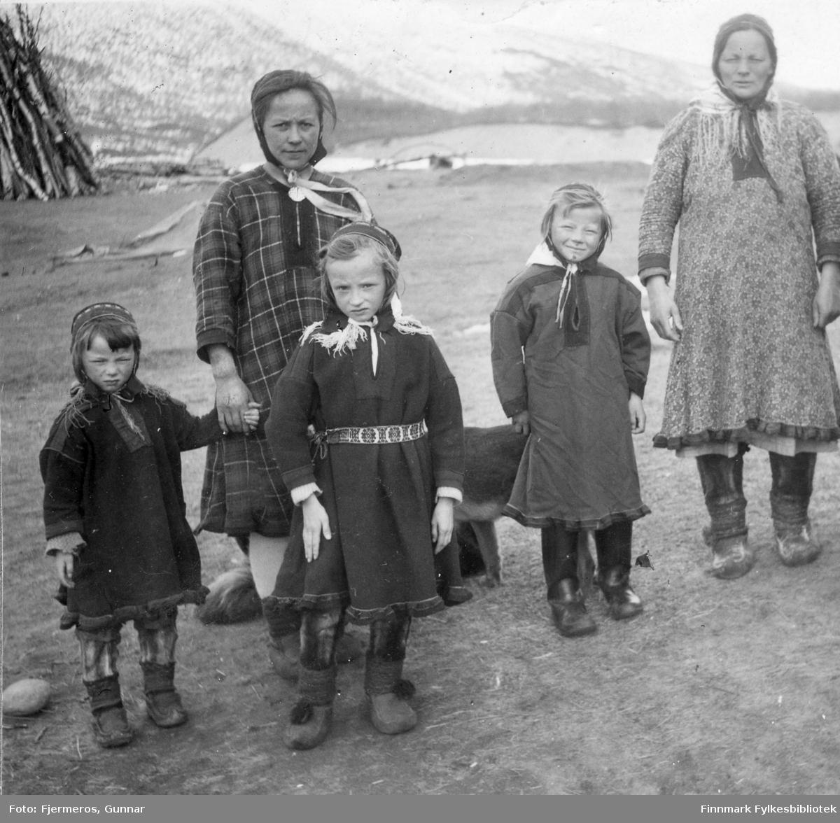 To kvinner og tre jenter (Guttorm familien) fotografert ved Levajok gieddi (Mikkelsen). Alle er kledt i sameklær og en hund står delvis skjult bak dem.