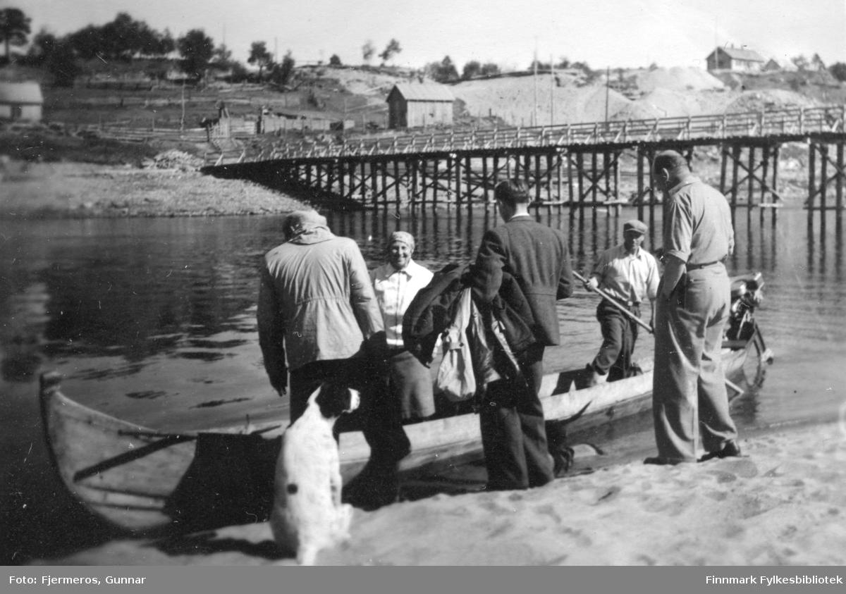Fem personer og en hund ved en elvebredd. To av dem står i en elvebåt. Sted og personer er ukjent.