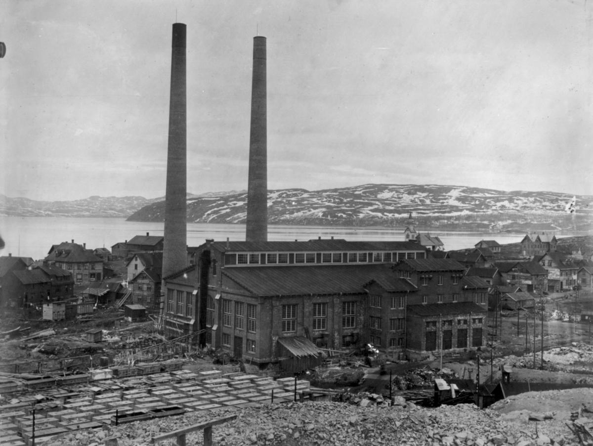 Dampsentralen i midten av bildet. Bak dampsentralen kan man se en kirke.