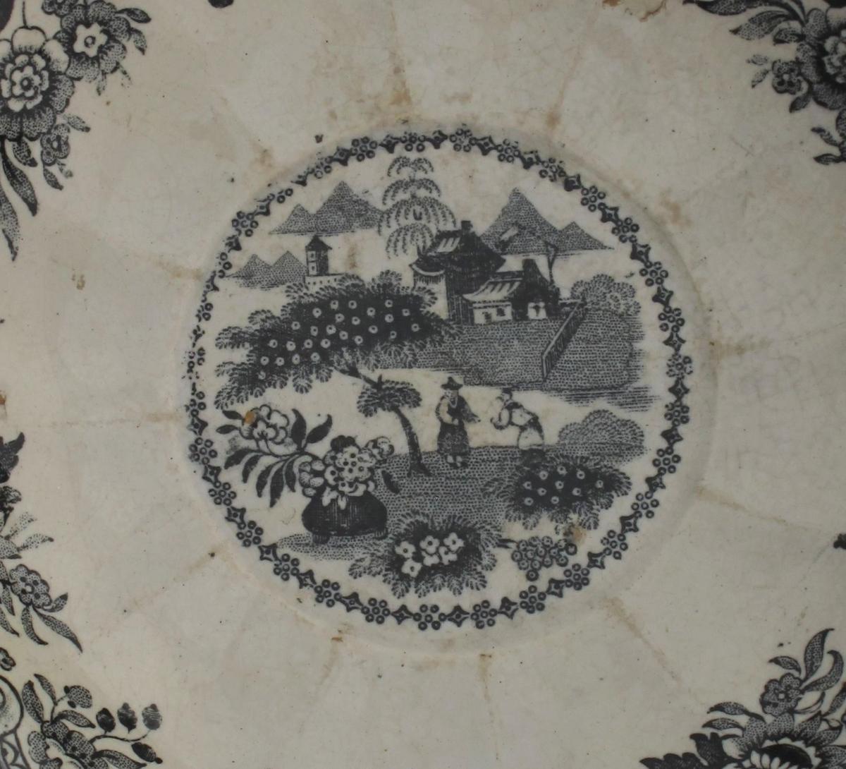 er buer ut mot munningen, inn mot insvunget fot, trykkt dekor  i sort; landskap m fjell i bakgrunnen, hus , trær og blomsterkrukker i forgrunnen, skal forestille kinesisk landskap; innv. ved munningen pseudo - rokokko ornamenter og blomster, i bunnen landskap ;: hus