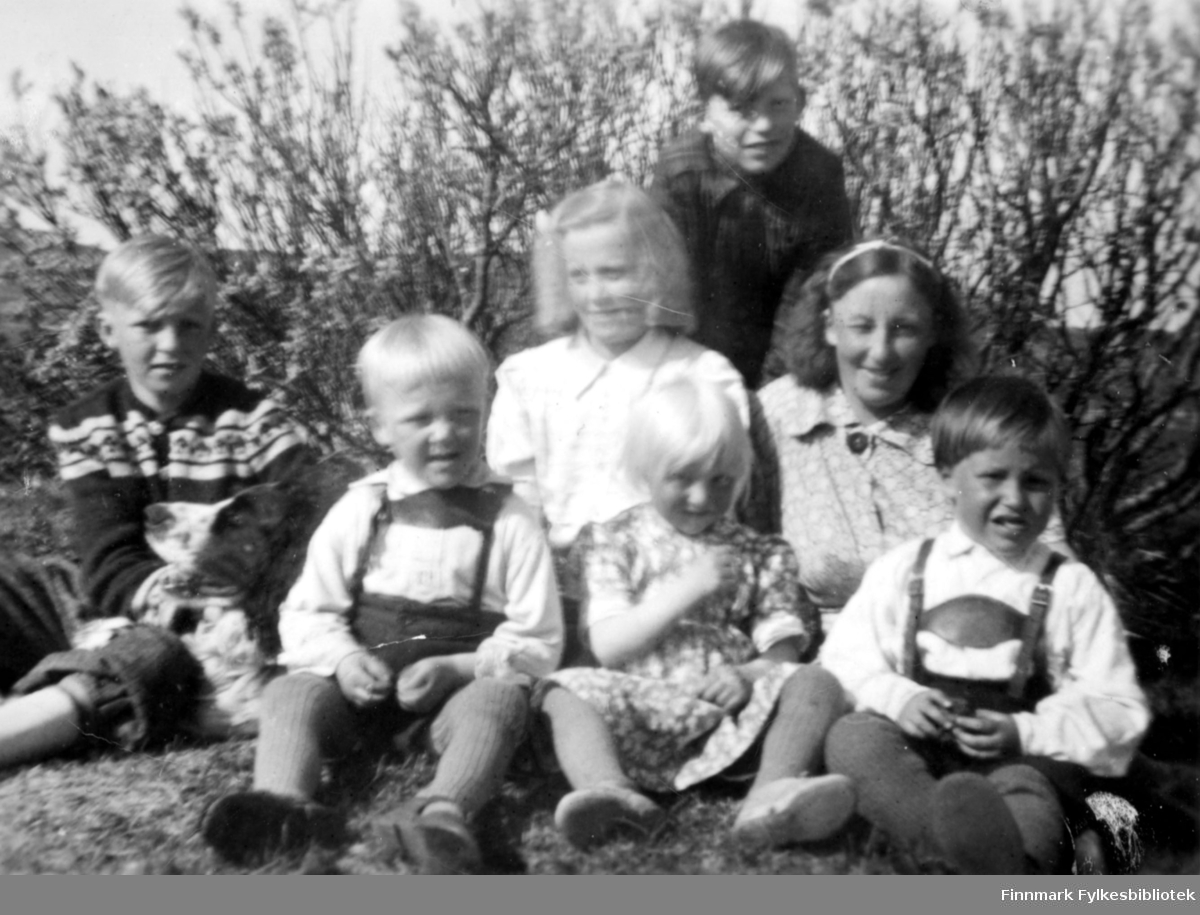 En kvinne og seks barn poserer for fotografen en sommerdag i Komagvær. Bakerst, iført mørk skjorte, sitter Arne Bendksen. De andre er, fra venstre: Einar Hagala, Steinar Hagala, Rut Hagala, Ranveig Hagala, Gudrun Bauna og Håkon Bauna.