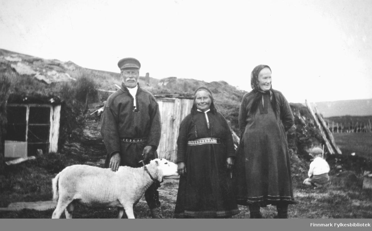 """""""Fra venstre: Mikkas Halonen, hans lille kone Anna og """"Gallas-Mari"""" foran Mikkas-gammen i Skittenelv. I bakgrunnen: Else-Liv Indrevær. """"Gallas-Mari"""" bodde i Klubben der Sigmund Pedersen bor i dag."""""""
