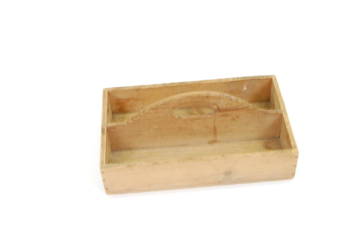 Form: rektangulær kasse med langsgående deling som er høyere enn kantene ellers og har et håndtak
