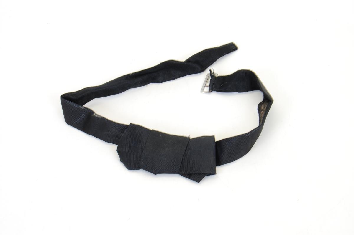Form: sløyfe festet på et bånd til å ha rundt halsen