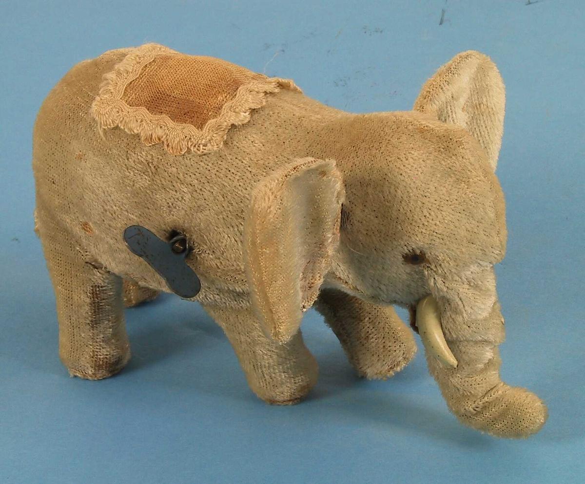 Lys grå elefant med brunt deksel over ryggen, buet snabel som beveger seg sammen med bena etter opptrekking.  Lekeelefant, Lys grå  plysj, litt brunt tynt stoff, innvendig  mekanisme med blå opptrekksskrue.