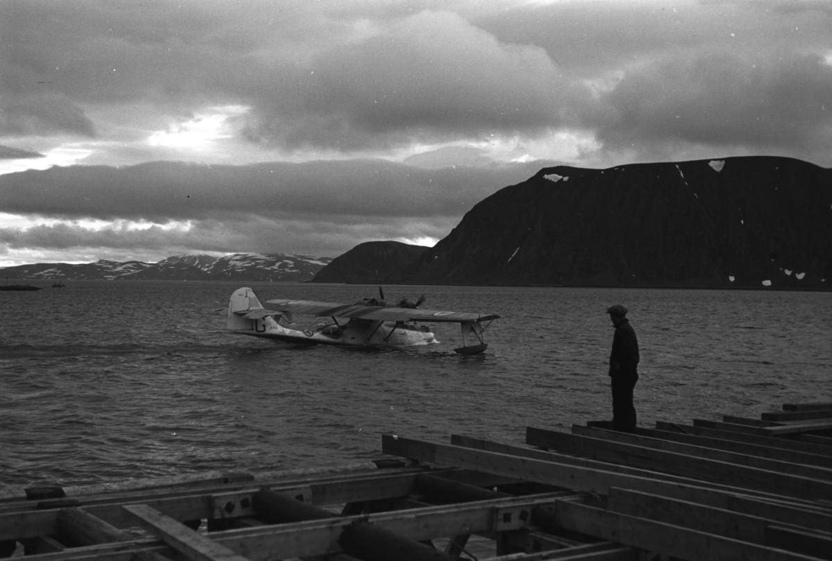 """En flybåt, muligens en Catalina, takser ute på fjorden ved Honningsvåg. Foran på bildet er en kai under byggning. En person står på land og betrakter det hele.   Flybåt er et fly som starter og lander på sjøen. En flybåt skiller seg fra et sjøfly ved at selve skroget flyter på vannet, skroget er dermed formet som på en båt. Eksempler på flybåter er for eksempel Short Sandringham og Dornier Do X. Flybåtene var svært populære før nettet av flyplasser var skikkelig utbygd, og egnet seg bedre for langdistanseflygninger enn samtidige landbaserte passasjerfly. Arkitekt Ola Hanche-Olsen arbeidet ved Brente Steders Reguleringskontor i 1946. Hovedadministrasjon for gjenreisning av Nord-Troms og Finnmark ble lagt til Harstad og fikk navnet Finnmark kontoret. Landsdelen Nord-Troms og Finnmark blev oppdelt i syv distrikt med hver sin administrasjon. Honningsvåg, distrikt IV, skulle betjene Nordkapp, Lebesby, Porsanger og Karasjok kommune.  Ola Hanche-Olsen har tatt bildene. Han var født 13. mars 1920 i Borre, død 11. februar 1998 i Gjettum. Han var både arkitekt og barnebokforfatter. Han hadde artium fra 1939, arkitekteksamen fra NTH 1946 og arbeidet deretter ved Finnmarkskontoret 1946–48 før han etablerte egen arkitektpraksis. Han debuterte som barnebokforfatter i 1974 med lettlest-boka """"Knut og sjørøverne"""", og skrev i alt 12 bøker. Han var XU-agent 1944-45, og var også en aktiv fjellklatrer og friluftsmann. Ola var gift med Solveig Hanche-Olsen (f. Falkenberg); de fikk 3 barn, blant dem matematikeren Harald Hanche-Olsen."""