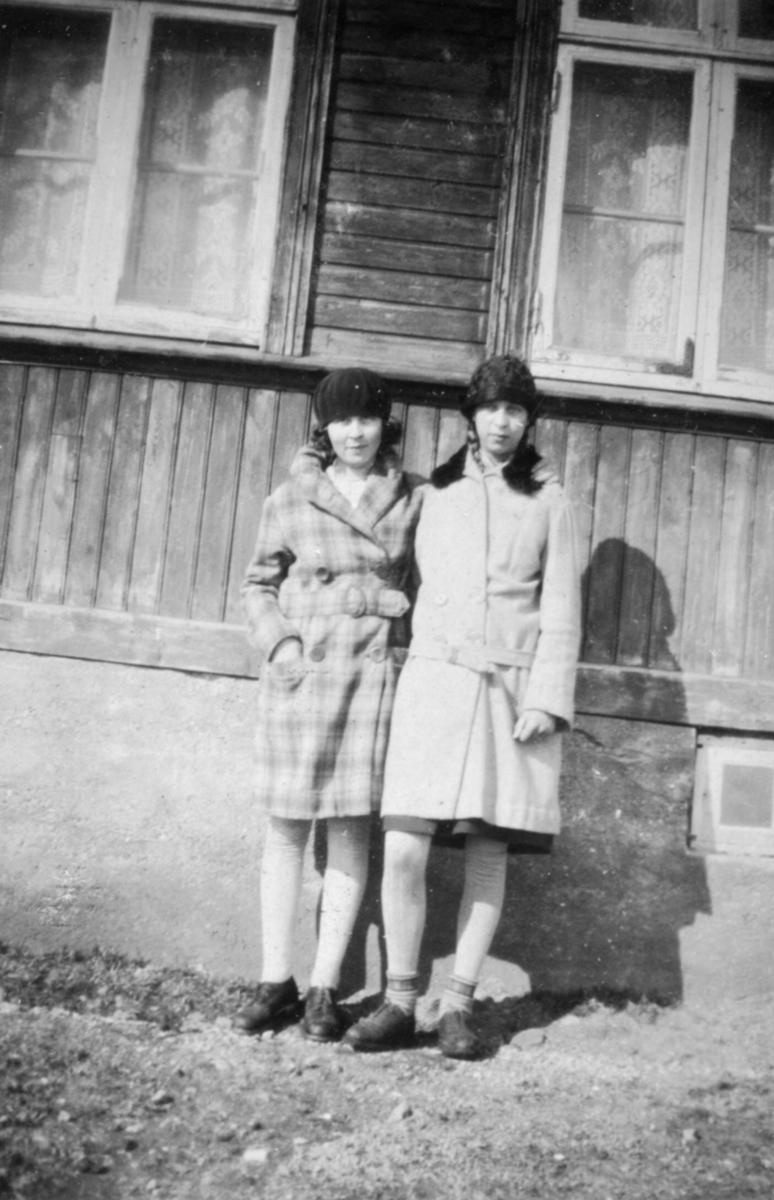 To jenter/unge damer fotografert utenfor et hus. Sted og personer er ukjent, men bildet er sansynligvis tatt i Kvalsund kommune før evakueringa.