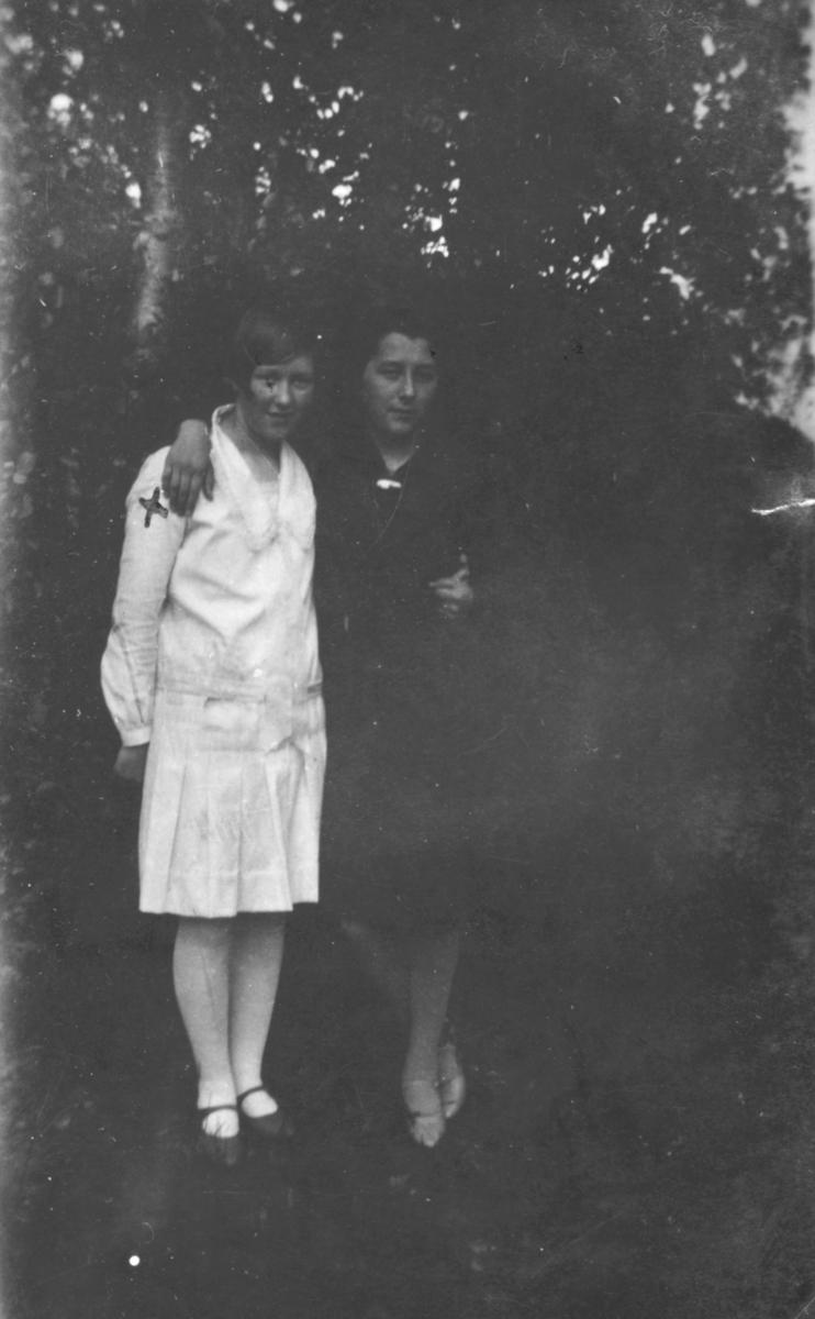 To unge kvinner fotografert foran noen trær. Sted og personer er ukjent.