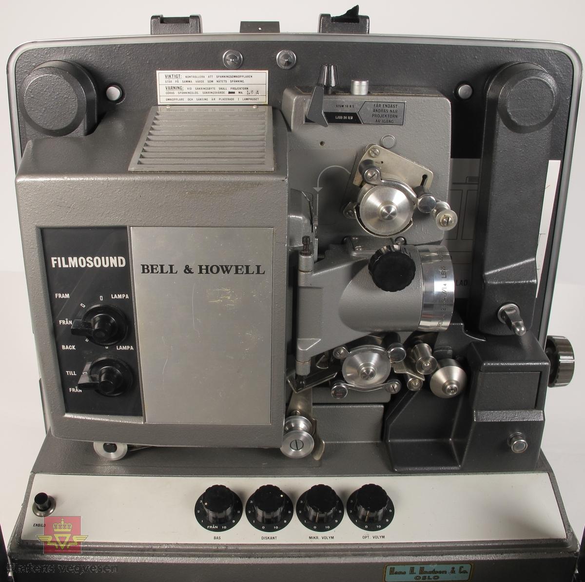 16 mm filmfremviser i mørk grå koffert av glassfiber, med defekt bærehåndtak. Den ene delen av kofferten har høyttaler av merket Goodmans, ledning for tilkobling av høyttaler og to klistremerker med påskrifter. Filmfreviseren har eget panel for justering av lyden. Bak på kofferten er det to skiltplater med innskrifter, MODEL 642 SK SERIAL No. K418 220V-1100 W - 50 ~ MADE IN ENGLAND og HANS H. KNUTSEN & CO. OSLO TYPE 642 No 418 P.VOLT 200/250 50 ~ S.VOLT AMP. 1200W. Veske, strømledning, ekstra lyspære og to tomme filmruller følger med filmfremviseren.