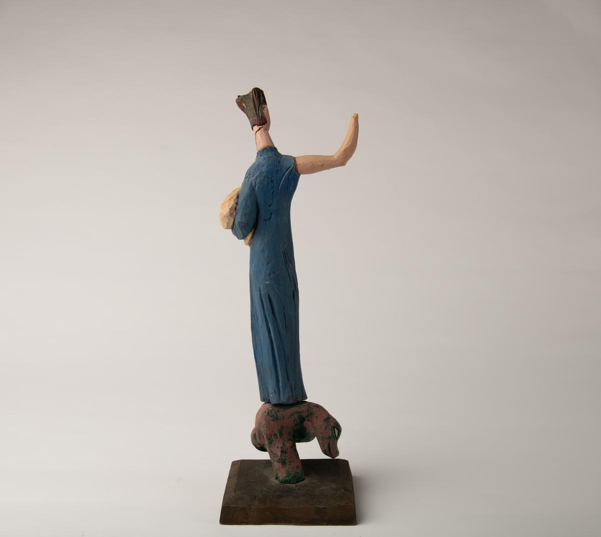 Lang smal kvinneskikkelse i blå kjole, gult