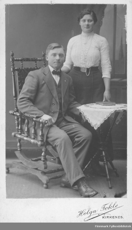 Fotoatelier portrett av en ung kvinne og en ung mann, muligens nygifte. Fotograf er Helga Tokle, Kirkenes.