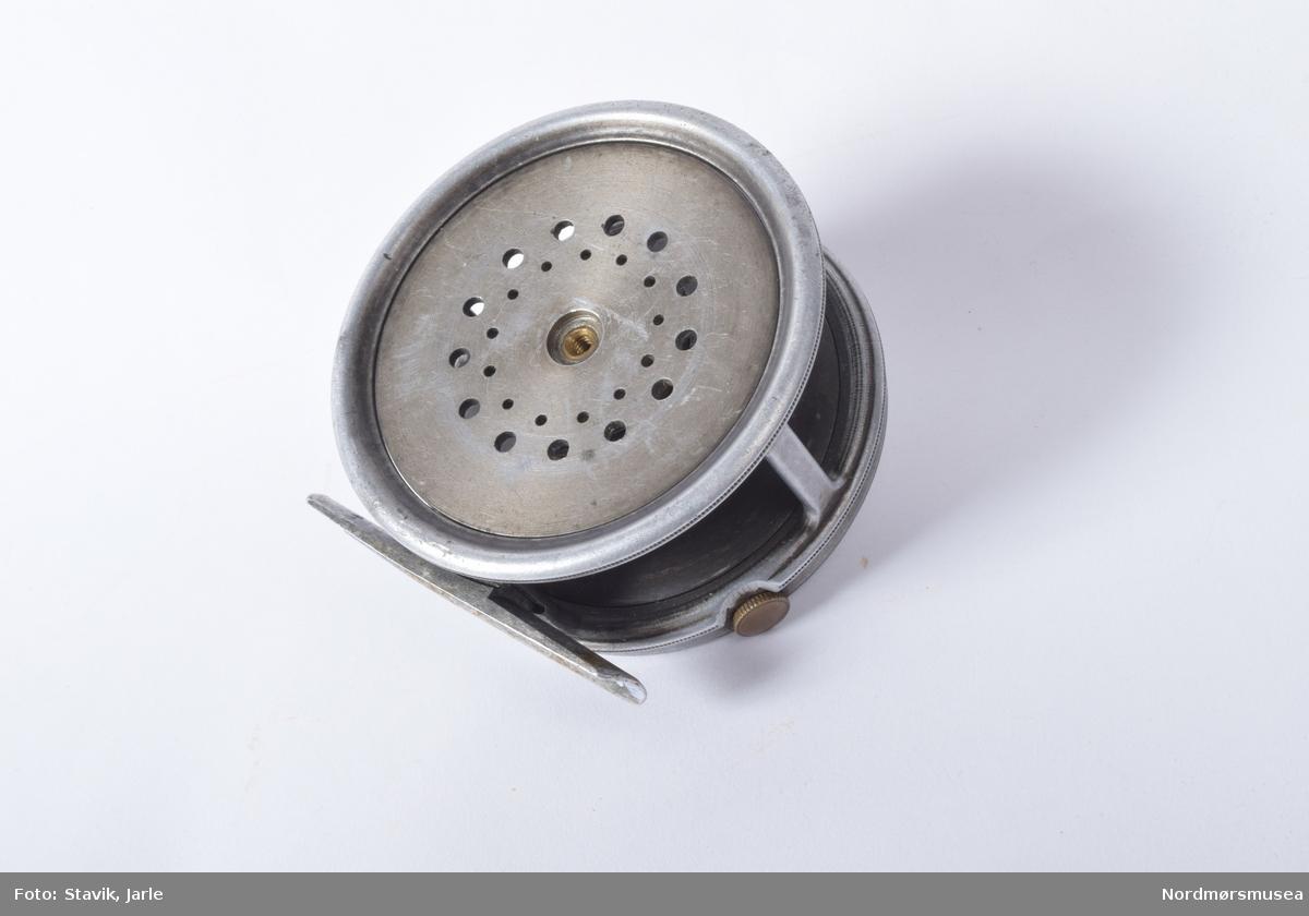 """Hardy """"Perfect"""" wide drum med originalt skinnfutteral fra Hardy. Snelle med glatt fot i legering. Singel 1917 brems på utsiden av trommelen innenfor sveivskiven. Hvit sveiv av ivorine montert på siden av sveivplaten. Produksjonsstempel, type på sveivplaten. Justering for bremsen på kanten. Ingen bro over kantjusteringsskruen var vanlig fra 1917-21. Futteralet er i god tilstand stemplet Hardy Bros LTD. Innmaten er lagd for at snellen skal passe og foret med rød plysj."""