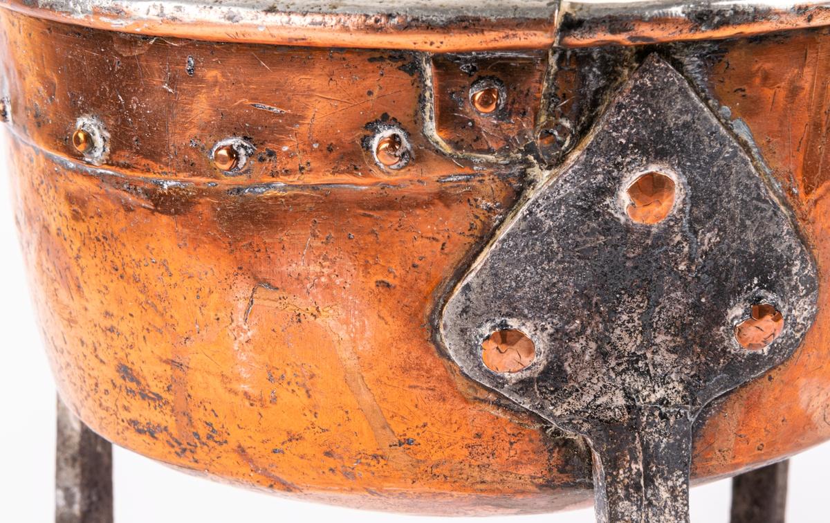 Trefotspanna i koppar, ben och handtag av järn. Stämpel M1 (otydlig).
