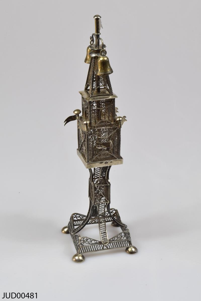 Kryddbössa tillverkad av silver, med genombruten filigrandekor. Dekrerad med flaggor i hörnen, samt två klockor och en flagga på toppen.
