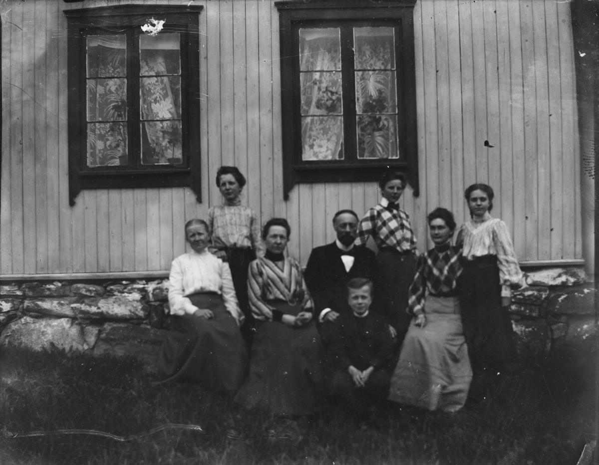 Gruppeportrett av en familie foran et hus