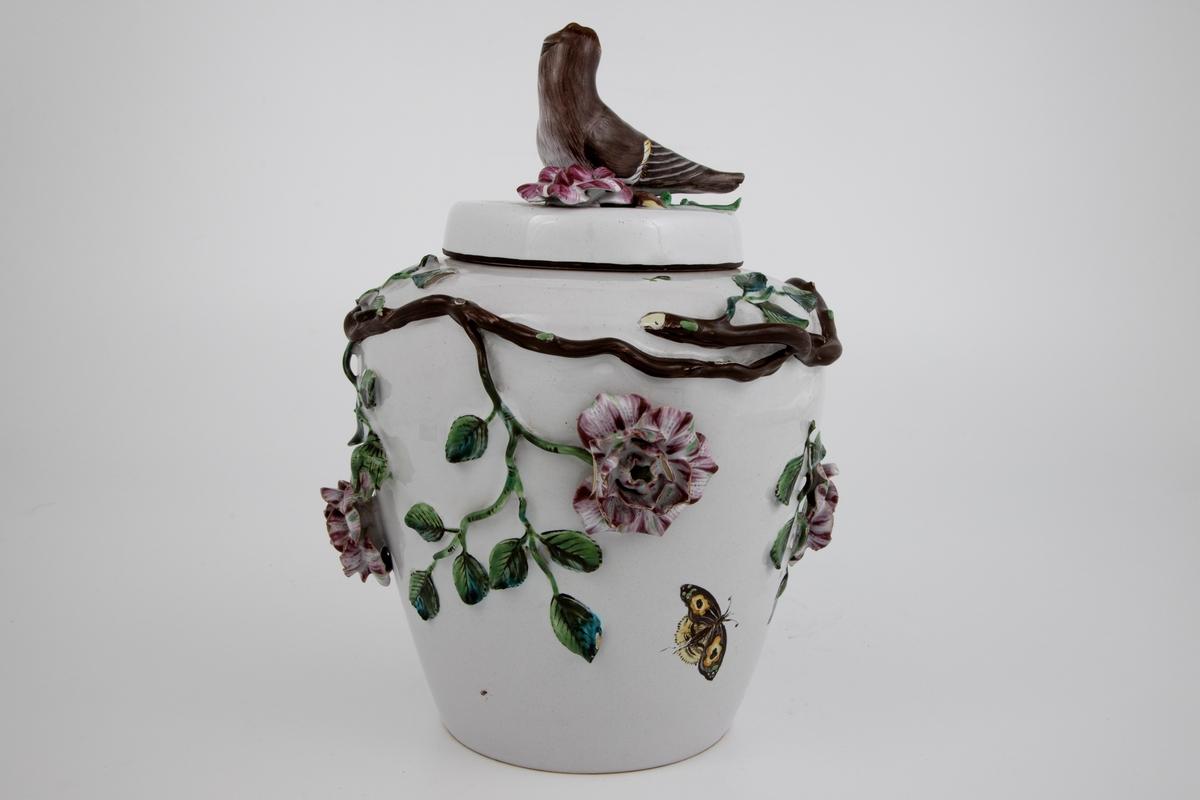 Krukke med kvister med grønne blader og rosalilla blomster på hvir grunn. På lokket en fugl.