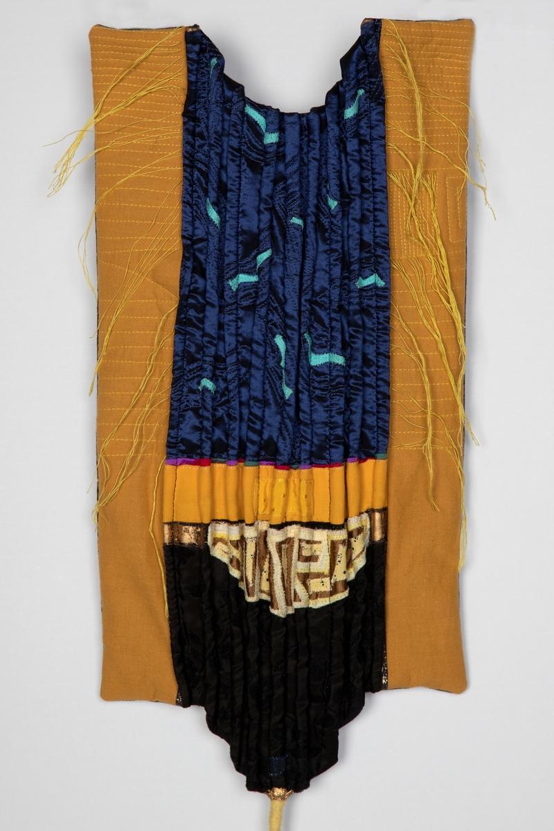 """Rektangulært, dekorativt tekstil i høydeformat. Flaten er delt i et mørk blåsvart, damasklignende midtfelt flankert av gule sidestykker. De gule sideflatene er maskinstukket med gule, tettstilte, vannrette sømmer. Disse er tettest i øvre del, og noe midre tett etter et opphold circa halvveis. Et lite parti på høyre side, er meget tett stukket med loddrette sømmer. Midtfeltet er foldelagt med stående """"roulorer"""" og maskinbrodert i turkis og svart. Øvre del av midtfeltet er også dekorert med små, turkisfargede applikasjoner mot det blåsvarte. Iflg tidligere katalogisering, er det gule og hvite maskinbroderier på feltet av gullbrokade. Endetrådene på stikningene er samlet i tynne fletter som ligger som et virvar på flatene. Nederst på tekstilet henger en svært lang, surret og flettet """"hale"""". Tekstilet har et japansk preg, og sammenfaller med de bølger av japonisme som også opptrådde i årene rundt 1990. Fôret med svart bomull. Kan virke noe vattert."""