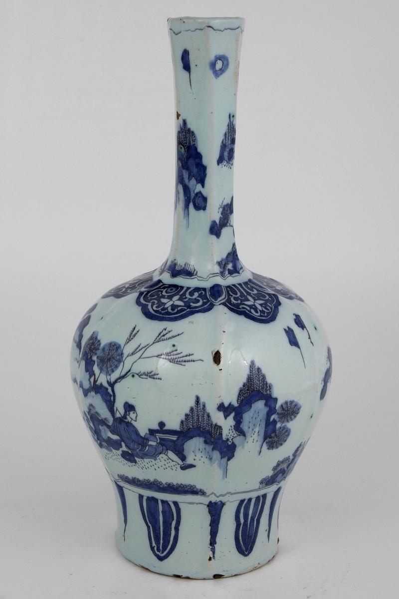 Heksagonal klubbeformet vase med kinesiskinspirert motiv med figur i landskap på både korpus og vasehals. En europeisk versjon av lingzhi/ ruyi-ornamentikk rundt vasehalsen på toppen av korpus.  Palmeblader nederst på vasen under hovedmotivet.