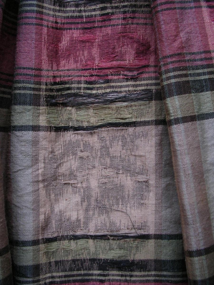 Klänning i halvylle; silkevarp. Mönstrad i rosa, grönt och svart med varptryck och rutor. Liv och ärmar fodrade.