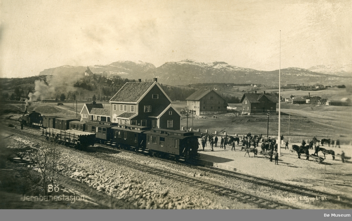 Bø jernbanestasjon med tog, folk og hestar.