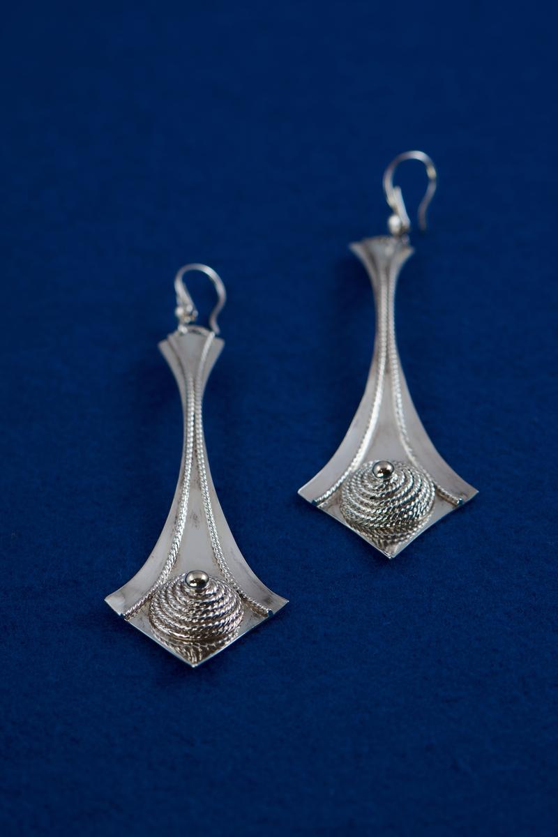 Örhängen i silver tillverkade av Rosa Taikon. De är dekorerade med en för Taikon karaktäristisk form: en spiral av filigrantråd omgärdar en minimal granalie av guld i spiralens mitt. De två örhängena har olika årsstämplar: F10 för 1980 respektive B11 för 2000.