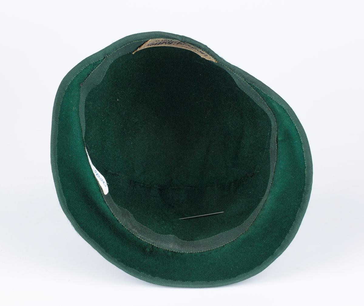 Hatt. Rundet. Nedover rundet brem foran. Foran sløyfe med 2 pynteknapper laget av tvunnet glassperlesnor.  Hattenål med hode av stoffet. Hatt til drakt/kåpe.