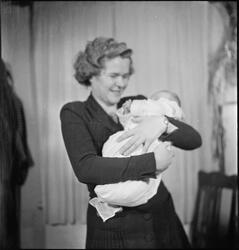 En kvinne med et nyfødt barn i armene. Bilde nr. 7 er av en