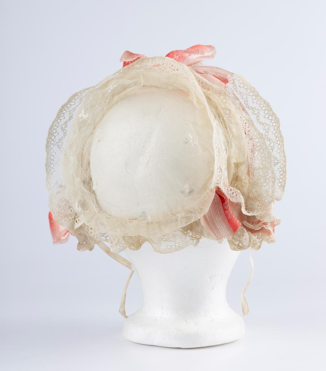 Hodekappe. Bøyle, pannestykke med 3 blonderader. Rosa sløyfe midt foran og ved ørene. Tyllstoff over bakhodet. Hodekappen og særlig blondene er stivet.
