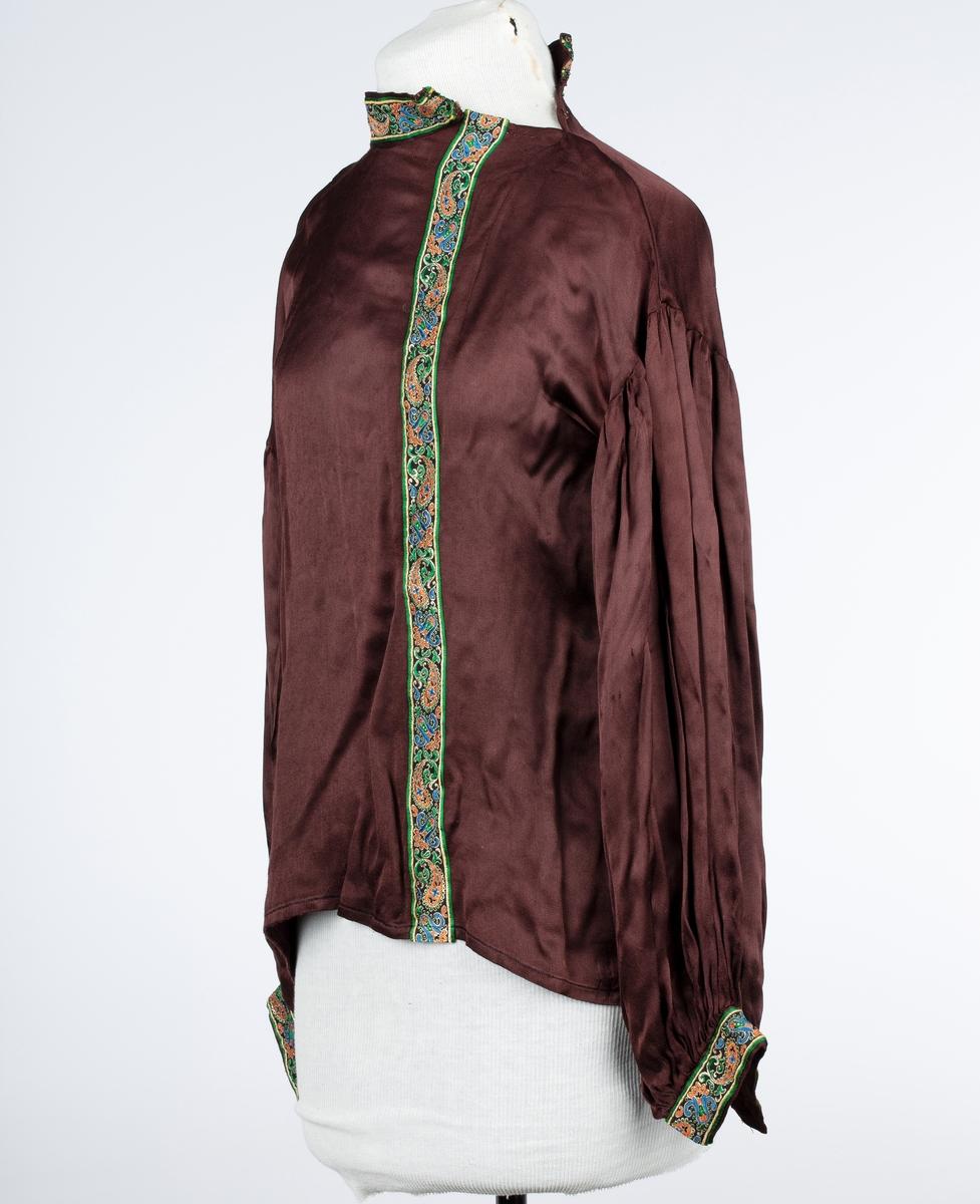 Rund, stående krage. Trykknapper på skulder. Posete, lange ermer. Bredt pyntebånd rundt halsen og nederst på ermene. Også vertikalt fra halsen og ned.
