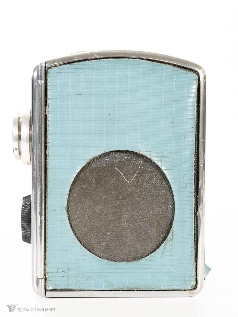 Rektangulært 8 mm filmkamera i metall kledd med nylonbelegg, med avrundet topp. Søker, indikatorvindu for filmlengde og åpningsknapp bak, og linse og velger for filmmetode i front. hengslet opptrekkshendel på høyre side.
