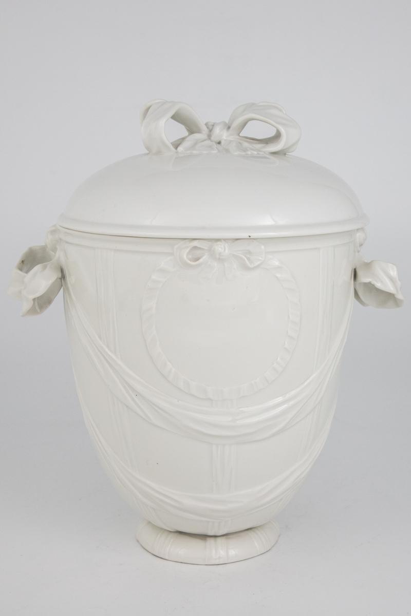 Eggformet monokrom hvit potpourrikrukke i en forenklet Louis XVI-stil. Håndtakene er formet som sløyfer. Ut fra disse sløyfene finner vi to draperte hengende bånd i relieff. Øverst på korpus finner vi en sløyfe med et sirkulært ubrutt bånd som former en medlajong. Dekorskjema er likt på begge sider av krukken. Knoppen på lokket er utformet som en sløyfe