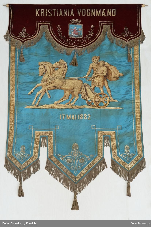A: faneduk i lys blå silke og rød fløyel. På forsiden en forgylt fremstilling av Apollon og Helios med påskrift. E1 og E2: Snorer med dusk tvunnet med metalltråd G-H: Snorer i bomull med dusk i rødt, hvitt og blått J-K: Gullfarget spir til fane L: Sort sørgeslør i tyll